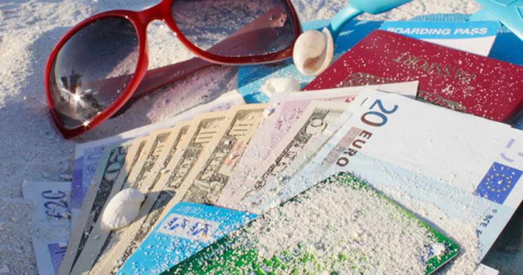 holiday-money-cards-and-sunglasses-on-a-beach-1024x538.png